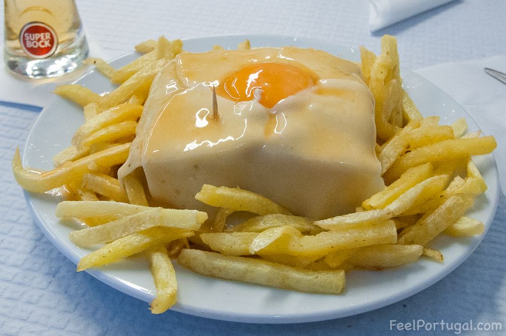 Francesinha sandwich with glass of draft beer